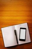 在一个开放空白的笔记本的手机 免版税库存照片
