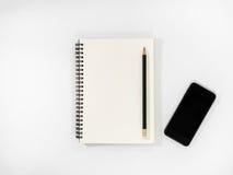 在一个开放笔记本上的黑铅笔 免版税库存照片