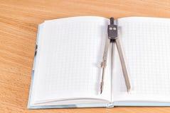 在一个开放笔记本的指南针 库存图片