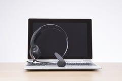 在一个开放膝上型计算机键盘的耳机 免版税图库摄影