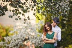 在一个开花的苹果的年轻人和妇女夫妇从事园艺 免版税库存照片