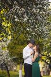 在一个开花的苹果的年轻人和妇女夫妇从事园艺 免版税图库摄影