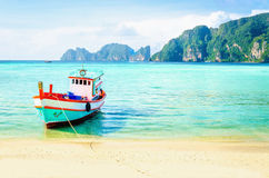 在一个异乎寻常的海滩的红色渔船,泰国 库存照片