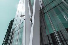 在一个当代企业摩天大楼的门面的一台唯一监视器在一好日子,在金属大梁的一部安全监控相机 免版税库存图片