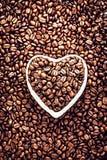 在一个心形的碗的烤咖啡豆情人节Ho 免版税库存照片