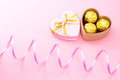 在一个心形的礼物盒的巧克力有卷曲丝带的 免版税库存图片