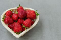 在一个心形的篮子的新鲜的草莓在桌上 库存照片