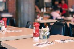 在一个快餐咖啡馆的表供食与蕃茄酱瓶子 图库摄影