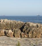 在一个恶魔葡萄牙的洞A嘴的岩石堤防有船的(Boca做地域)在背景中 免版税库存照片
