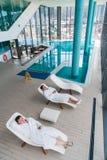 在一个懒人的两句年轻人谎言在一白色特里晨衣和放松的一个游泳池 免版税库存图片