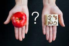 在一个成熟红色苹果和一个蛋糕之间的选择与奶油 图库摄影