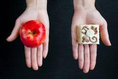在一个成熟红色苹果和一个蛋糕之间的选择与奶油 库存图片