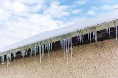 在一个房子屋顶的冰柱作为危险交通和步行者 免版税图库摄影