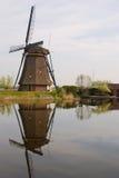 在一个房子旁边的一台风车与美好的水反射的kinderdijk的 库存照片