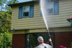 在一个房子的前面的一种重的超重白种人人喷洒的水解答作为他的压力洗涤的服务一部分的 库存照片