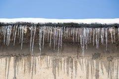 在一个房子的屋顶的冰柱在冬天 免版税图库摄影