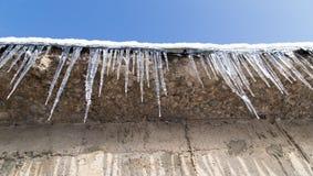 在一个房子的屋顶的冰柱在冬天 免版税库存图片