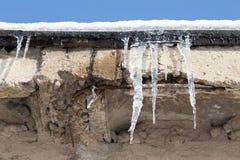 在一个房子的屋顶的冰柱在冬天 免版税库存照片