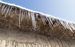 在一个房子的屋顶的冰柱在冬天 库存照片