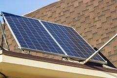 在一个房子的屋顶的太阳电池板反对蓝天的 库存图片