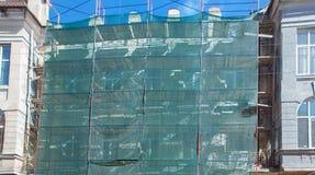 在一个房子附近的脚手架建设中外在膏药工作、高公寓在城市,白色墙壁和窗口的, ye 免版税库存图片
