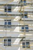 在一个房子附近的脚手架建设中外在膏药工作、高公寓在城市,白色墙壁和窗口的, ye 库存图片