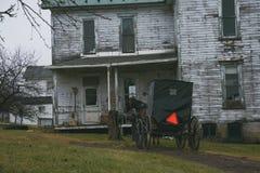 在一个房子附近的门诺派中的严紧派的儿童车在宾夕法尼亚 库存照片