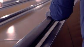 在一个手套的手在自动扶梯的栏杆,提高 影视素材