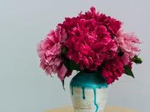 在一个手工制造花瓶的红色牡丹 库存照片
