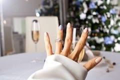 在一个手指的钻戒在圣诞树下 免版税库存图片