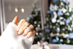 在一个手指的钻戒在圣诞树下 图库摄影