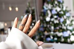 在一个手指的钻戒在圣诞树下 库存图片