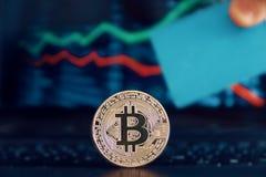 在一个手提电脑键盘的Bitcoin货币反对股票市场概念的波动价值图 有卡片的手 库存图片