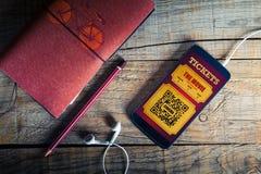 在一个手机屏幕的戏院票在一张木桌 免版税库存照片