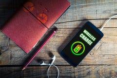 在一个手机屏幕的无线充电在一张木桌 免版税库存照片