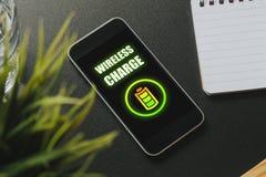 在一个手机屏幕的无线充电在一张黑企业桌 免版税库存照片