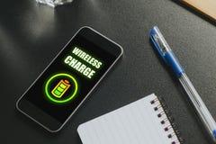 在一个手机屏幕的无线充电在一张黑企业桌 免版税库存图片