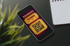 在一个手机屏幕的电子戏院票被安置在一张黑书桌 免版税图库摄影