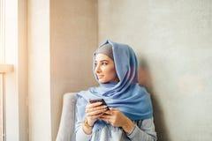 在一个手机的回教妇女传讯在咖啡馆 免版税库存照片