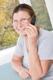 在一个手机的年长妇女razgovariet 免版税库存照片