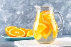 在一个投手的橙色戒毒所水在灰色具体背景 健康食物,饮料 免版税库存照片