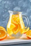 在一个投手的橙色戒毒所水在灰色具体背景 健康食物,饮料 图库摄影