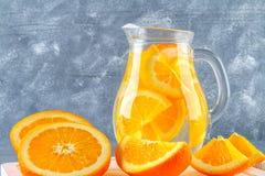 在一个投手的橙色戒毒所水在灰色具体背景 健康食物,饮料 免版税库存图片