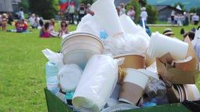 在一个拥挤容器的塑料和纸垃圾在咖啡馆旁边的公园 影视素材