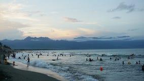 在一个拥挤海滩的日落与小波浪 图库摄影