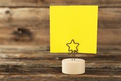 在一个持有人的黄色便条纸在棕色木背景 免版税图库摄影