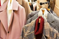 在一个挂衣架的妇女的外套在服装店 图库摄影