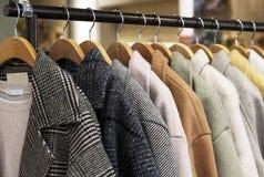 在一个挂衣架的妇女的外套在服装店 免版税库存图片