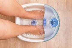 在一个振动的脚按摩器的女性脚 电按摩脚浴 修脚和脚关心 免版税库存照片