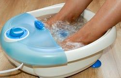 在一个振动的脚按摩器的女性脚 电按摩脚浴 放松工作 免版税库存图片
